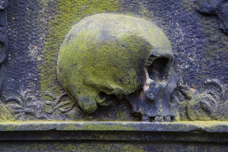 Skalleskulptur på en grav royaltyfria foton
