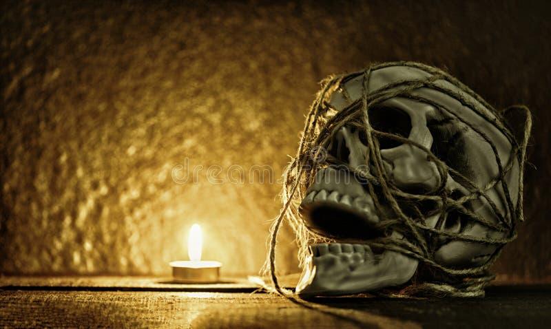 Skallestilleben/m?nsklig skalle med repet som dekoreras omkring p? det halloween partiet och den ljusa stearinljuset p? m?rker royaltyfri bild