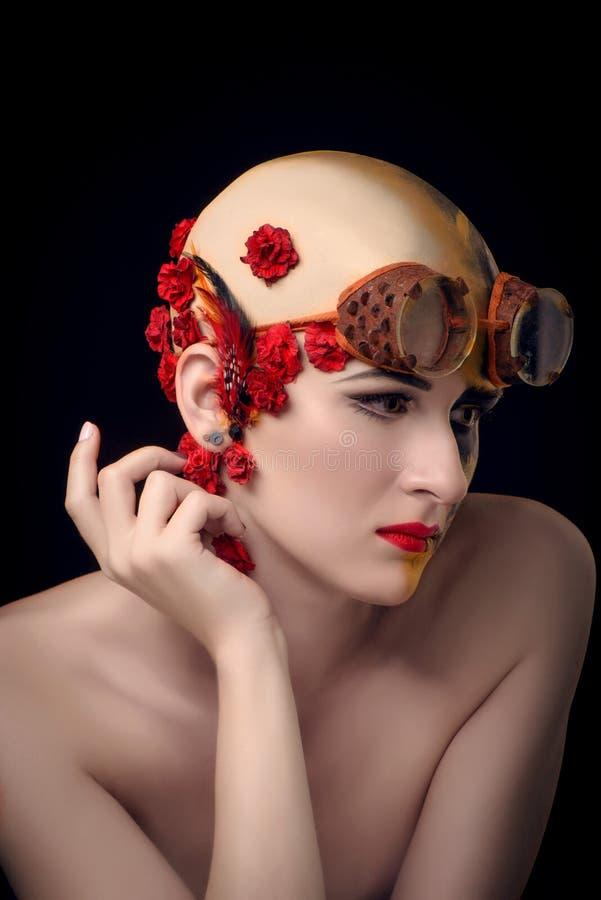 Skallig flicka med ett konstsmink och steampunkexponeringsglas arkivbild