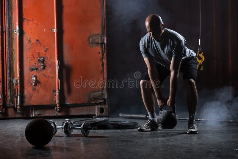 Skallig karismatisk idrottsman nen som gör squats med vikter fotografering för bildbyråer