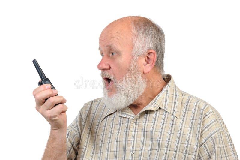 Skallig man för pensionär som skriker till walkie-talkie arkivfoto