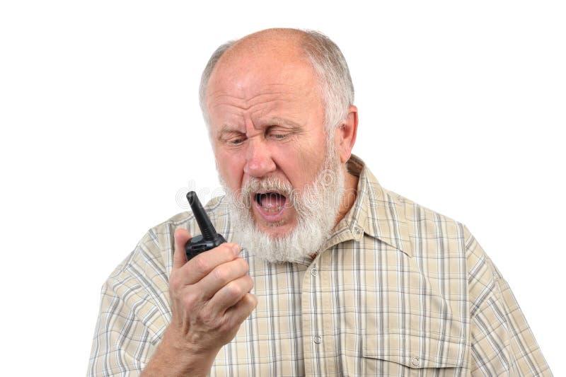 Skallig man för pensionär som talar genom att använda walkie-talkie royaltyfri foto