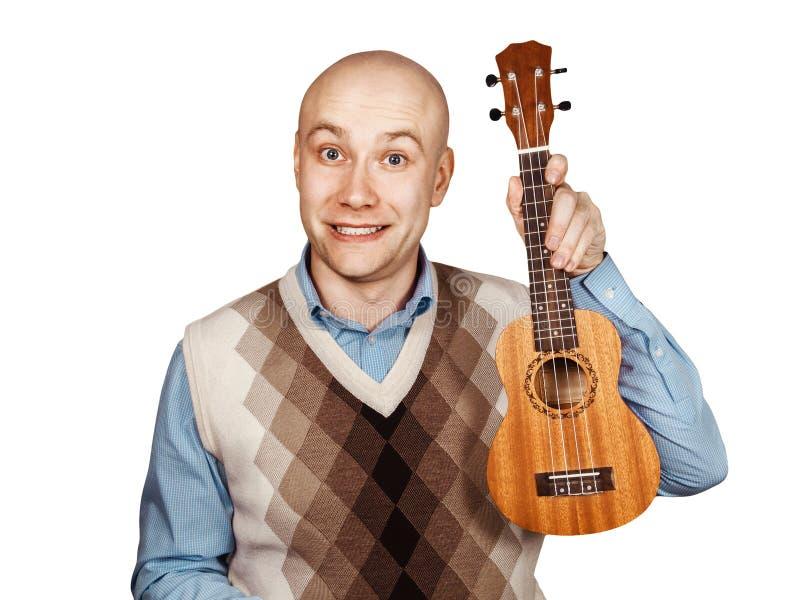 Skallig man för stående med ukulelet på vit isolerad bakgrund arkivfoton