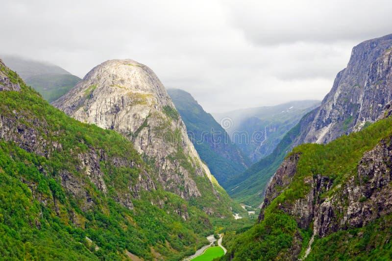Skalligt berg i en grönskande dal fotografering för bildbyråer