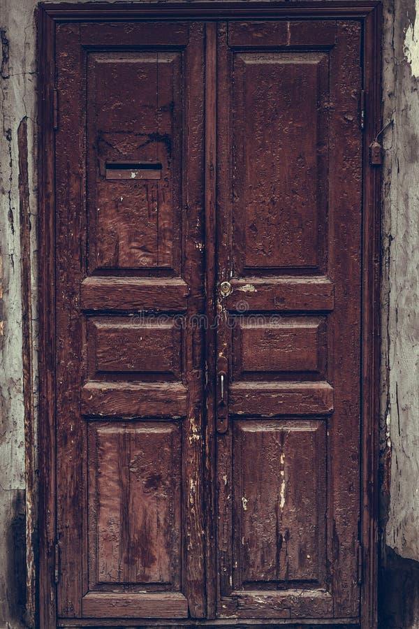 Skalning av den bruna trädörren Förfallen trägrungedörr med sprucken rödbrun målarfärg Trådslitet mörkt - röd dörr fotografering för bildbyråer