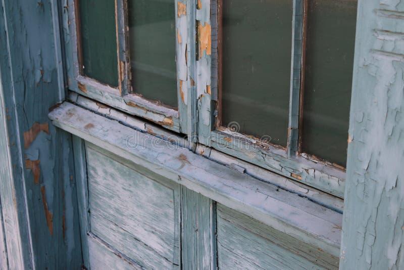 Skalning av målarfärg på gammalt fönster arkivbild