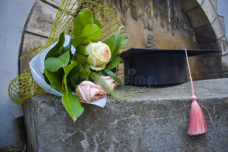 Skalowania mortaboard z wiązką róże na starych schodkach w skalowanie dniu lub nakrętka zdjęcia royalty free
