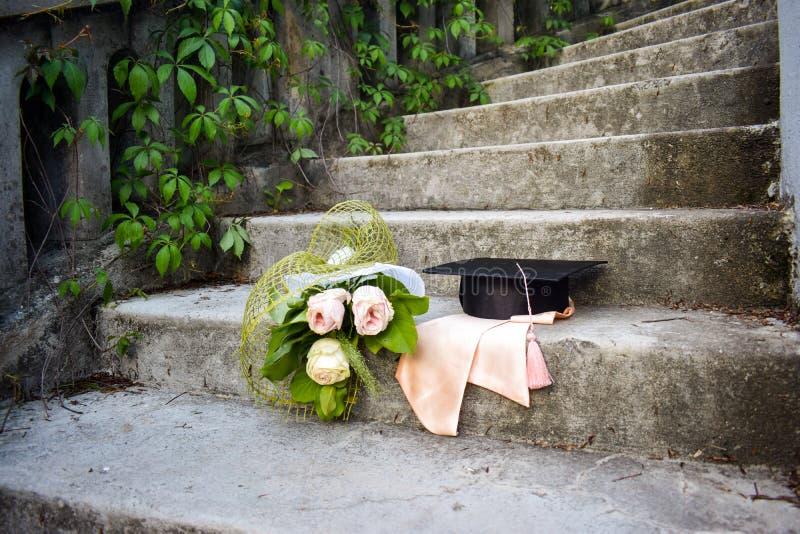 Skalowania mortaboard z wiązką róże na starych schodkach w skalowanie dniu lub nakrętka obrazy stock