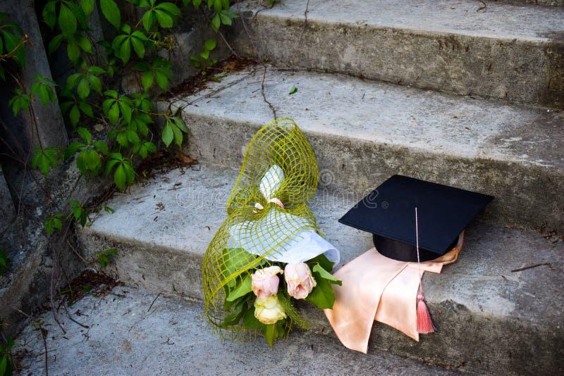 Skalowania mortaboard z wiązką róże na starych schodkach w skalowanie dniu lub nakrętka fotografia stock