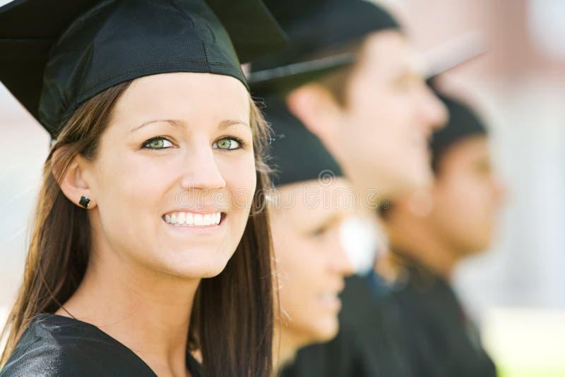 Skalowanie: Ładni absolwentów spojrzenia Przy kamerą zdjęcia royalty free