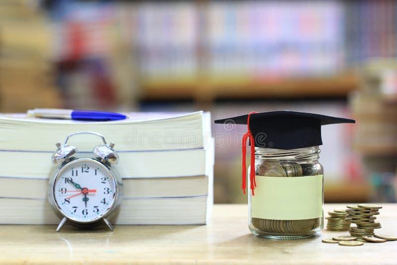 Skalowanie kapelusz na szklanej butelce na p??ka na ksi??ki w bibliotecznym izbowym tle, Ratuje pieni?dze dla edukaci poj?cia fotografia stock