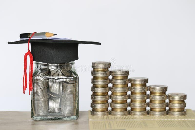 Skalowanie kapelusz na szklanej butelce z stertą moneta pieniądze na wtite tle, Ratuje pieniądze dla edukacji pojęcia obrazy stock