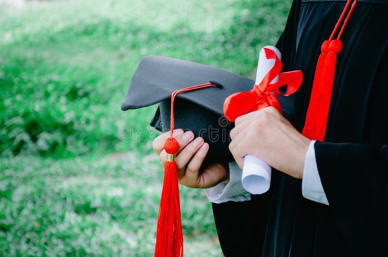 Skalowanie, Studenccy chwytów kapelusze i dyplom w ręce podczas początku sukcesu absolwentów uniwersytet, obrazy stock