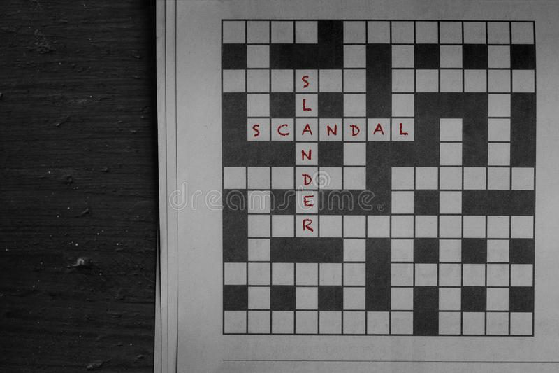 Skandal i obmawianie pisać w czerwieni gazetowa crossword łamigłówka gdy rozwiązania fotografia royalty free