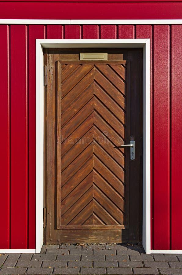 Skandinav-stil ljus röd och vit fasad med den bruna träfiskbensmönsterdörren arkivfoto
