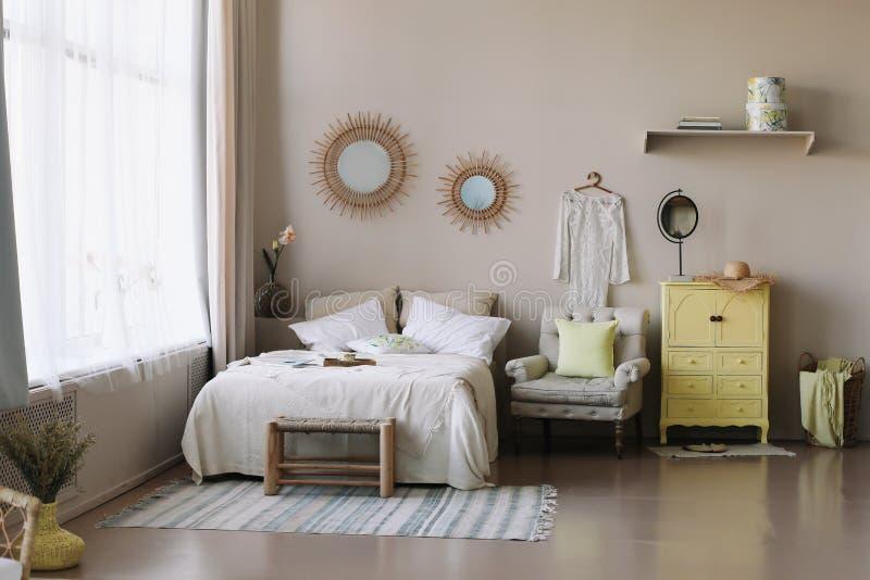 Skandinavisch modern comfortabel binnenland Breed bed met hoofdkussens, leunstoel en decoratie in slaapkamer royalty-vrije stock foto's
