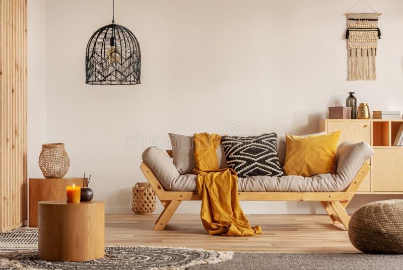 Skandinavische bank met hoofdkussens en donkere gele deken in helder woonkamerbinnenland met zwarte kroonluchter royalty-vrije stock foto's