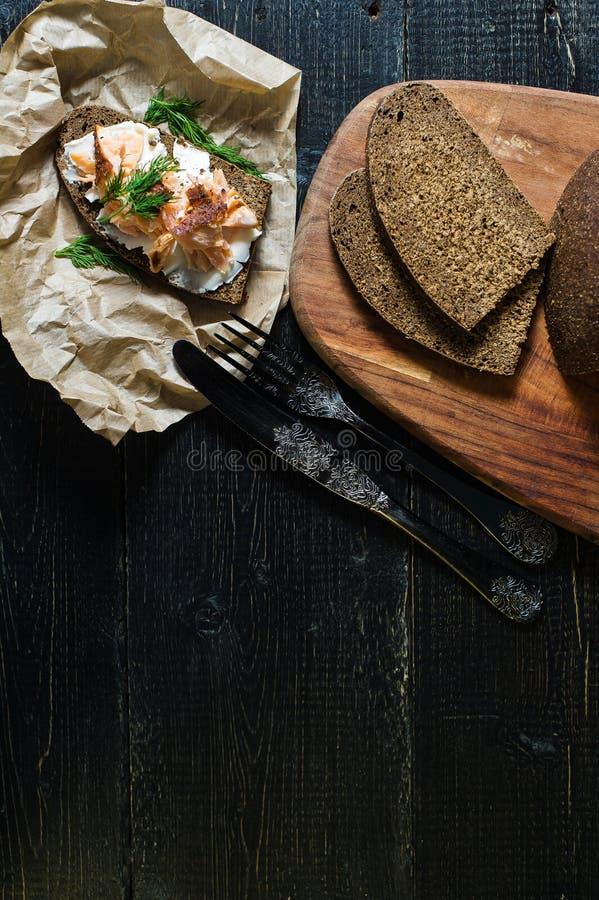 Skandinavische sandwich met gerookte zalmfilet op zwart brood met zachte kaas royalty-vrije stock foto