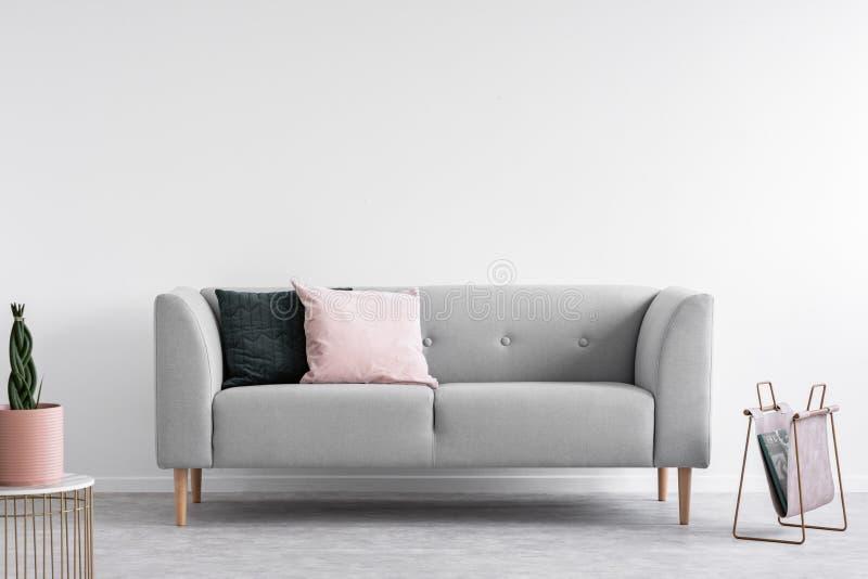 Skandinavischer minimaler Entwurf mit grauem Sofa, wirkliches Foto mit Kopienraum auf der Wand lizenzfreie stockfotografie