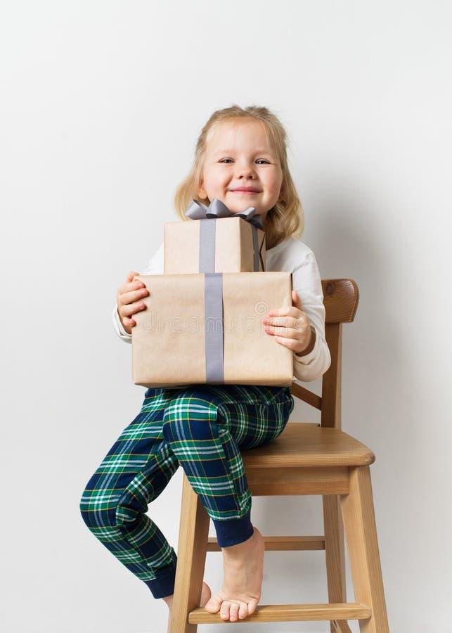 Skandinavisk minimalismjul och begrepp för nytt år med ungen - liten flicka med bunten av gåvaasken på en stol i rum som är vit arkivfoton