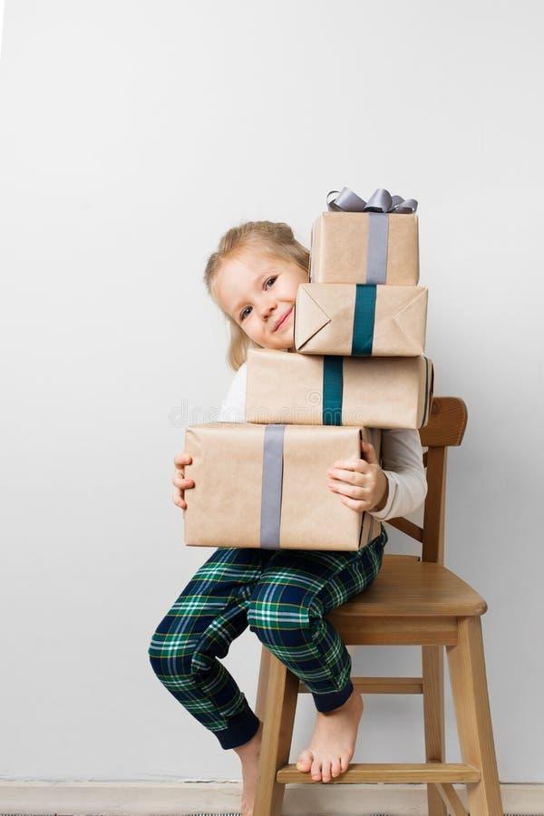Skandinavisk minimalismjul och begrepp för nytt år med ungen - liten flicka med bunten av gåvaasken på en stol i rum som är vit arkivfoto