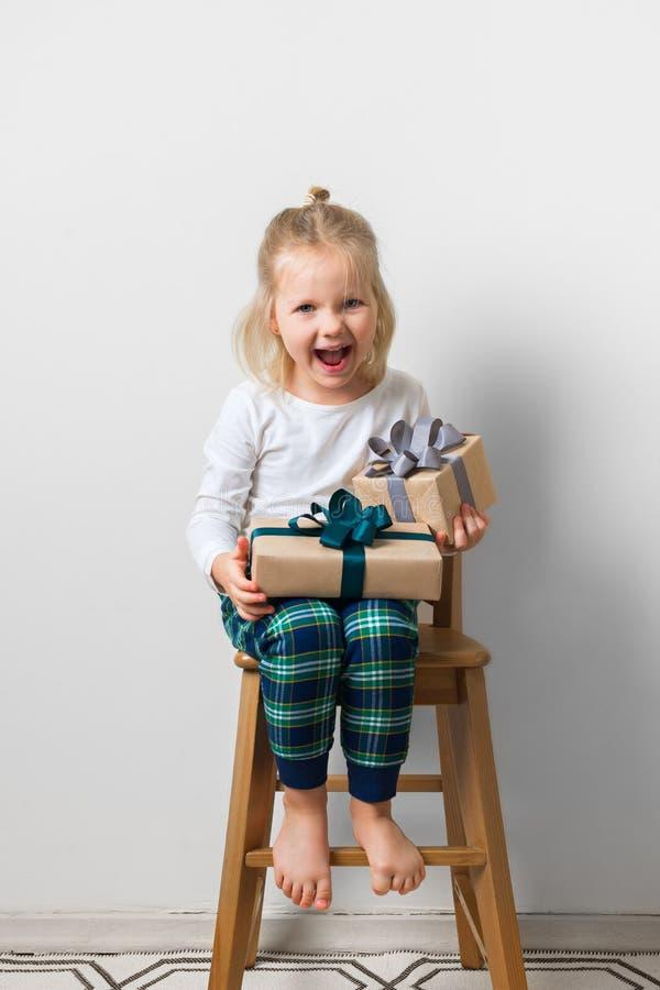 Skandinavisk minimalismjul och begrepp f?r nytt ?r med ungen - liten flicka med bunten av g?vaasken p? en stol i rum arkivbild