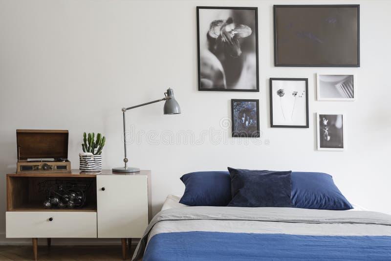 Skandinavisk stil, träskänk vid en marinblå säng och inramad konstgalleri på en vit vägg av ett idérikt sovrum arkivbilder