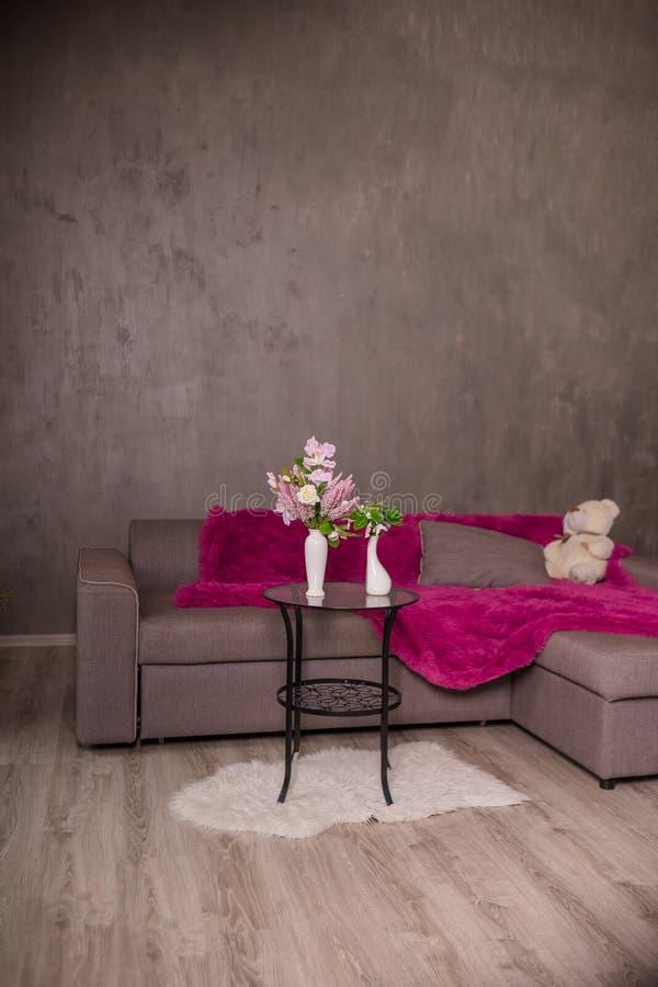 Skandinavisk vardagsrumdesign som är inre med soffan och den runda tabellen med blommabuketten Braun soffa med plädet, kuddar, na royaltyfri bild