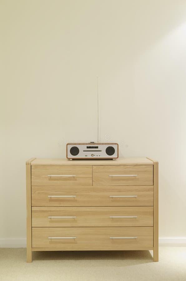 Skandinaviska enheter för bröstkorg för ekbokträdmöblemang i sovrummet som är inre hemma med musikCD-spelare royaltyfri fotografi