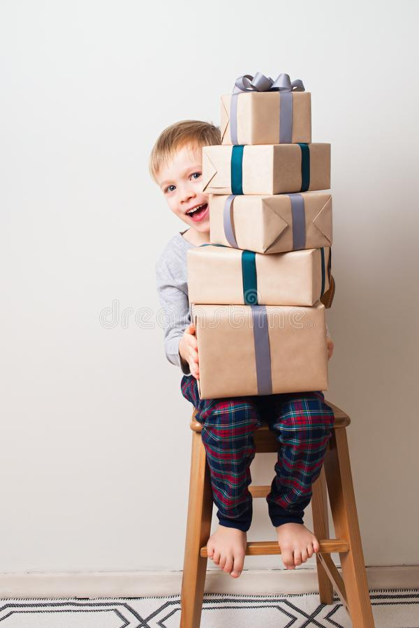 Skandynawscy minimalizmów boże narodzenia i nowego roku pojęcie z dzieciakiem - chłopiec z prezenta pudełkiem na krześle w pokoju fotografia stock