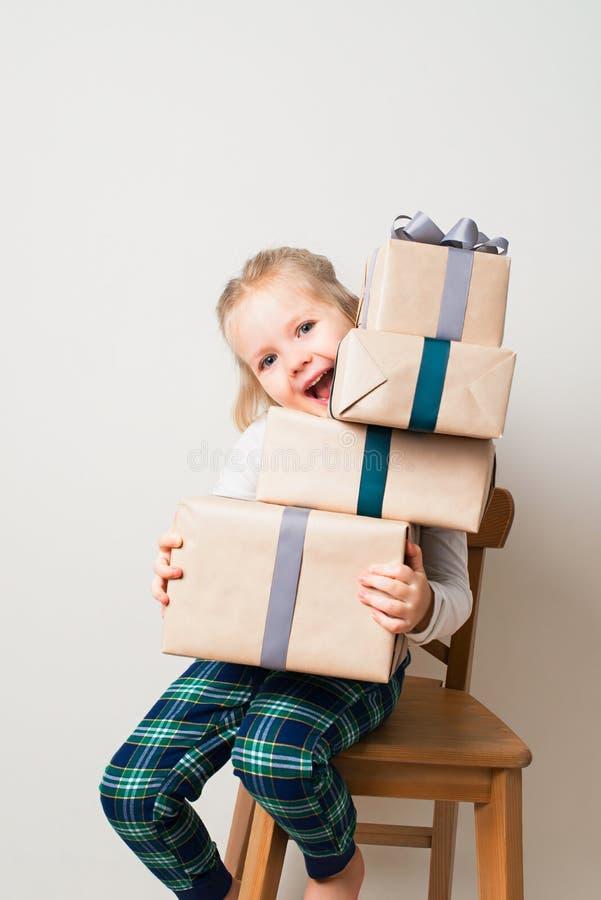 Skandynawscy minimalizmów boże narodzenia i nowego roku pojęcie z dzieciakiem - mała dziewczynka z stertą prezenta pudełko na krz zdjęcie royalty free