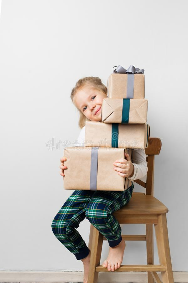 Skandynawscy minimalizmów boże narodzenia i nowego roku pojęcie z dzieciakiem - mała dziewczynka z stertą prezenta pudełko na krz zdjęcie stock