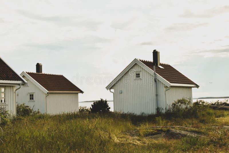 Skandynawski nadmorski krajobraz z pięknymi białymi drewnianymi chałupami fotografia stock
