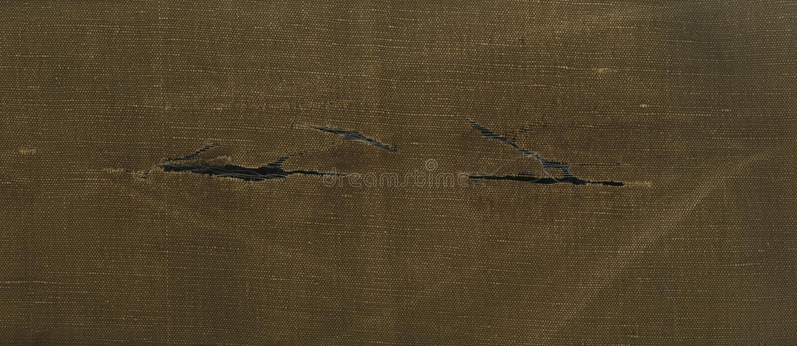 Skanirovaniya texture rough yellow brown torn tissue is tarpaulin. Direct scan is long and narrow ( panoramic ) pieces of canvas ( denim ) fabric with rips stock photo