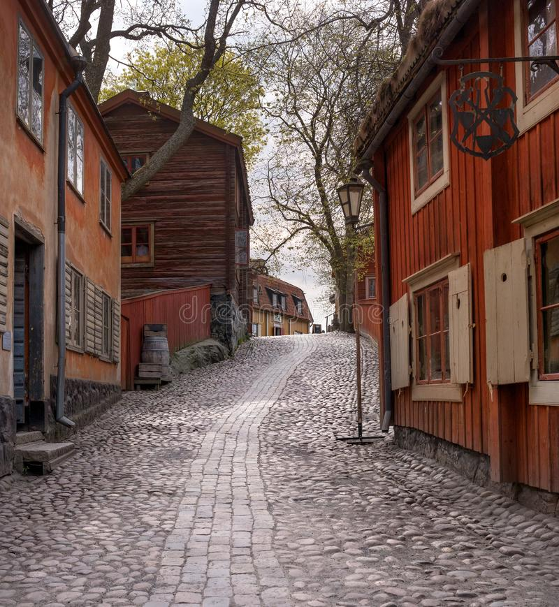 Skansen, the world`s oldest open-air museum. Old Swedish buildings. Cobblestone street. Old Swedish street. Stockholm. Sweden royalty free stock images
