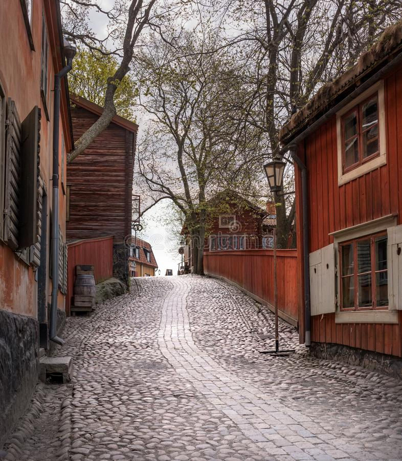 Skansen, the world`s oldest open-air museum. Old Swedish buildings. Cobblestone street. Old Swedish street. Stockholm. Sweden stock image