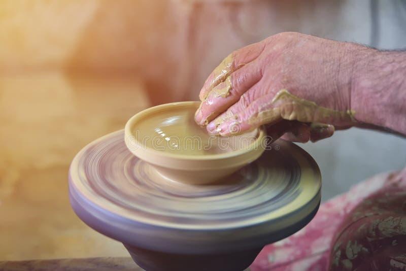 Skapa en krus eller en vas av den vita leranärbilden Manhänder, keramiker royaltyfria foton