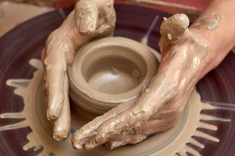 Skapa kruset eller vasen av lera Kvinnahänder, hjul för keramiker` s arkivbilder