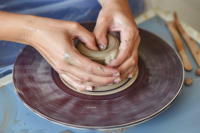 Skapa kruset eller vasen av lera Kvinnahänder, hjul för keramiker` s royaltyfria bilder