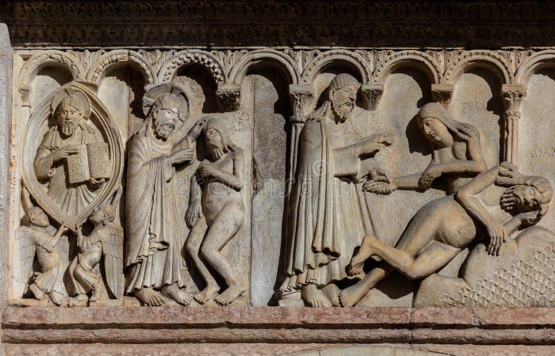 Skapelse och nedgång på Modena'sens domkyrkafasaden arkivfoto