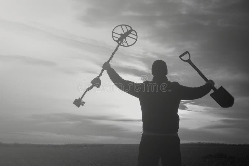 Skarbu myśliwy z wykrywacz metalu na fazującym pszenicznym polu w poszukiwaniu przygody przeciw backlight słońce obrazy royalty free