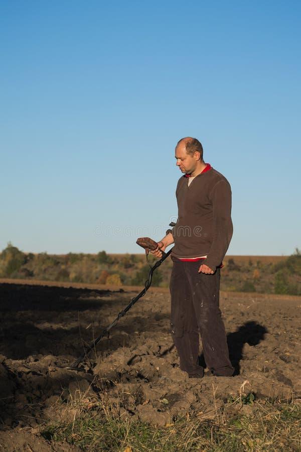 Skarbu myśliwy z wykrywacz metalu w jego rękach z poważną twarzą skanuje ziemię fotografia stock