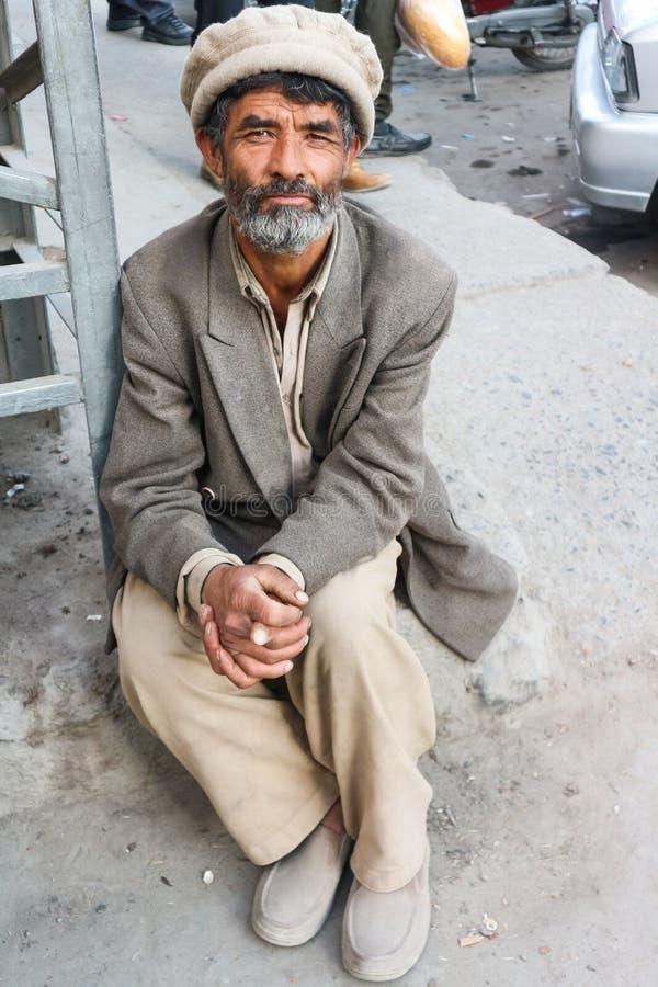 SKARDU PAKISTAN - JULI 28: En oidentifierad gamal man poserar för en stående, som han vilar efter hårt arbete Juli 28, 2018 i Ska arkivfoto