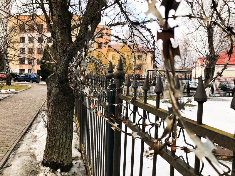 Skarp farlig skyddande taggtråd för järnmetall på staketet med grova spikar och insatser mot himlen royaltyfri fotografi