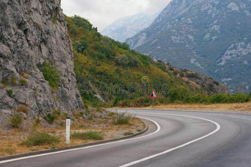 Skarp vänd av vägen med ett tecken av fallande stenar Balkans M royaltyfria bilder