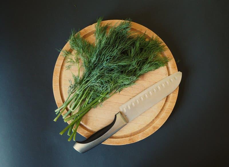 Skarp yrkesmässig kockkniv på en grupp av ny grön dill arkivbilder