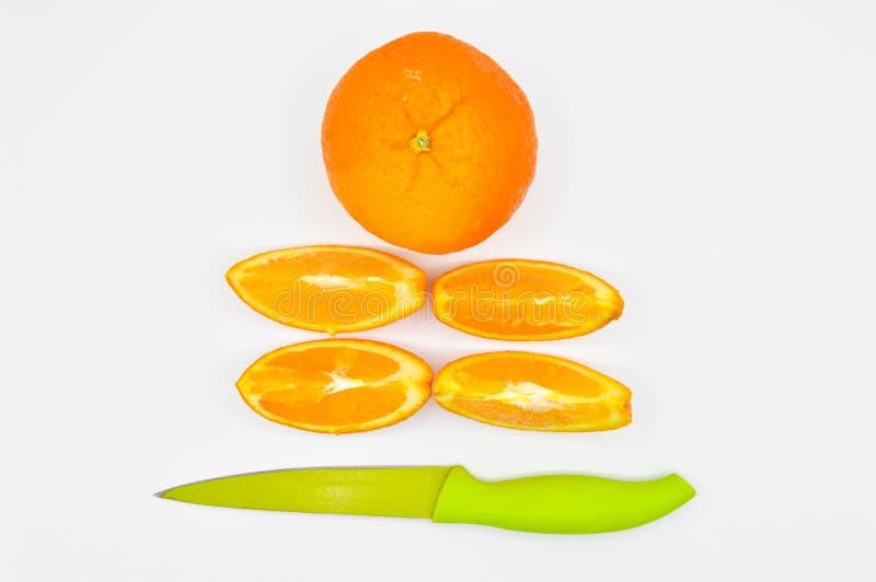 Skarpa klippta orange skivor som ?r nya och som ?r saftiga och en kniv royaltyfri foto