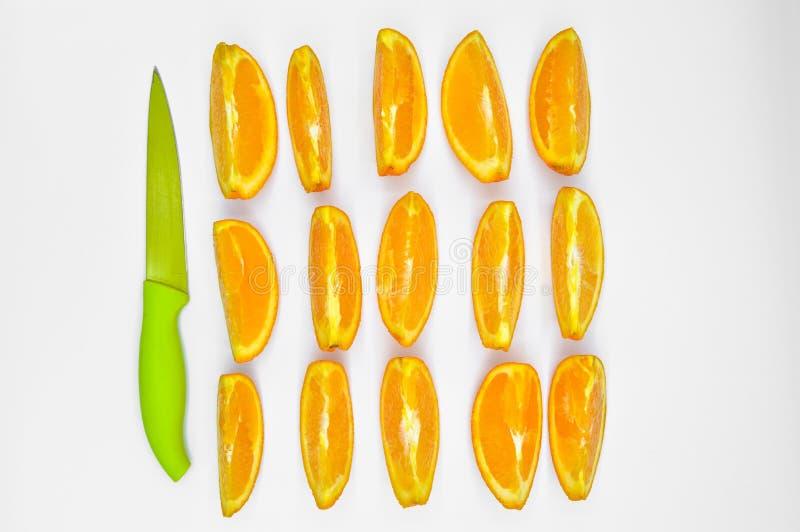 Skarpa klippta orange skivor som ?r nya och som ?r saftiga och en kniv Diet- och att banta fotografering för bildbyråer