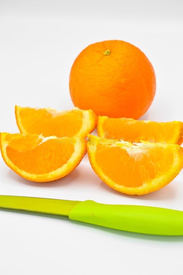 Skarpa klippta orange skivor som ?r nya och som ?r saftiga och en kniv arkivbild