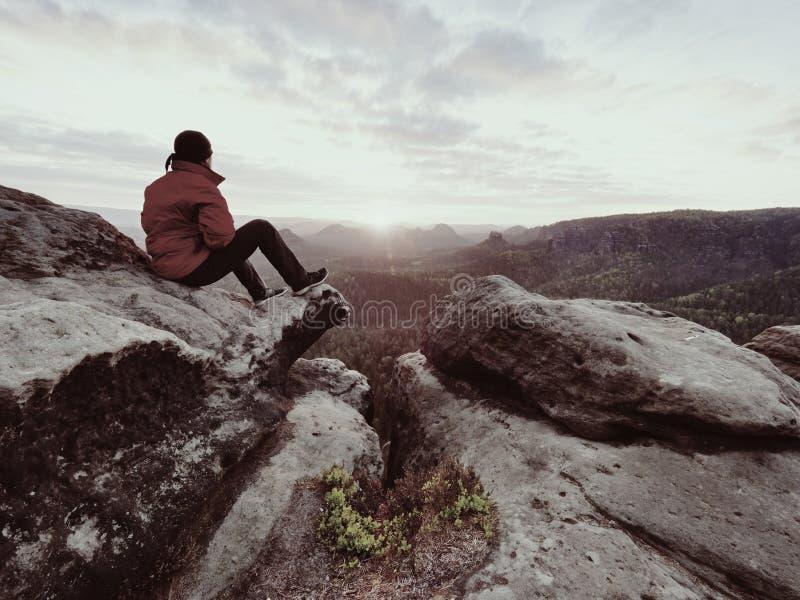 Skarpt stenigt maximum ovanför bergdalen, kall sol som döljas i regniga moln royaltyfri foto